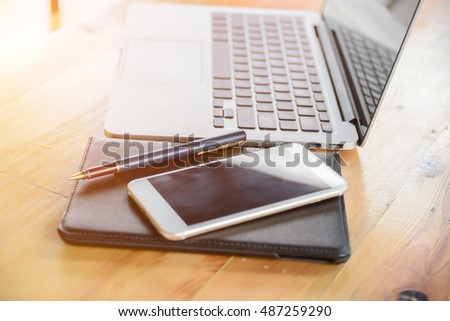 business woman hoding pen with notebook and phone on wooden table