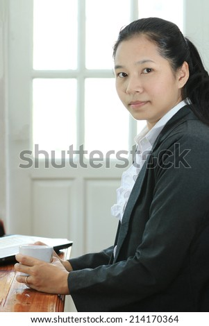 Business woman hold a coffee cup, office location background.