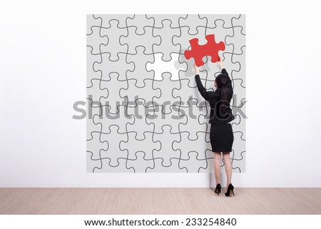 business woman hold jigsaw puzzle - Back view of business woman making a puzzle on the wall - stock photo