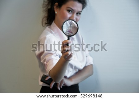 Business woman hold magnifier and a mobile phone