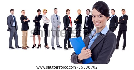 Business woman holding a clipboard with her team behind