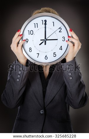 business woman holding a clock up to her face shot in the studio on a grey background - stock photo