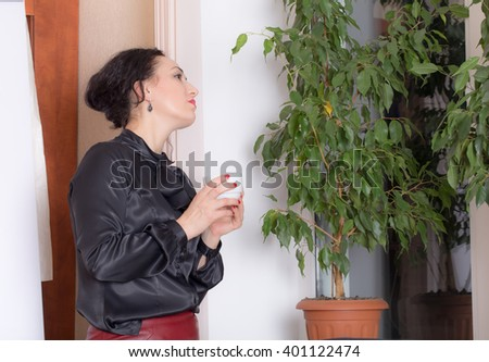 Business woman holding a cup and looking at the window. Photo can be used as a whole background.