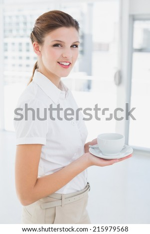 Business woman holding a cup and smiling
