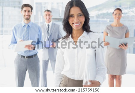 Business woman holding a folder in front of fellow workers - stock photo