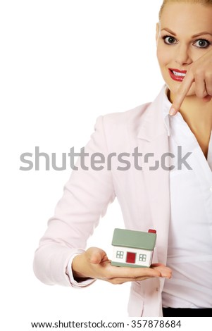 Business woman holding a house model.