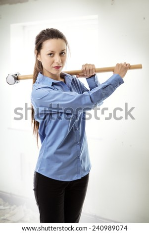 business woman holding a large sledgehammer get ready for trouble - stock photo