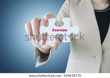 Business woman holding a piece of jigsaw puzzle with word Overview