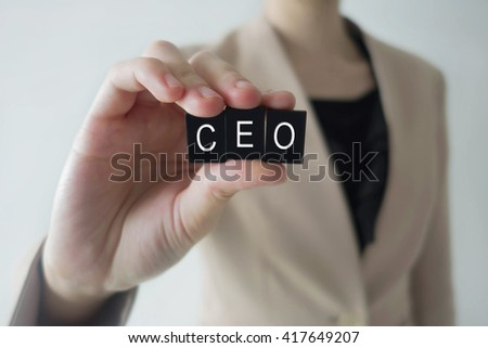 Business woman holding acronym CEO letter against a defocussed background with cool image temperature