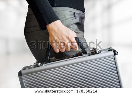 Business woman holding an aluminium briefcase. - stock photo