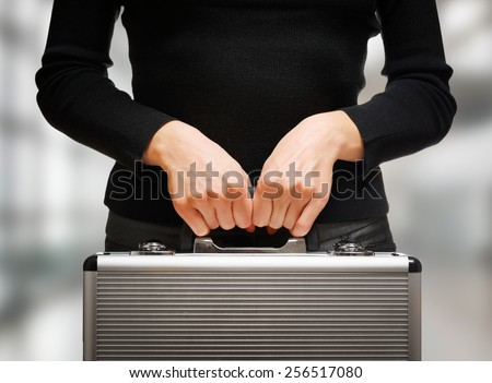 Business woman holding an aluminum briefcase and preparing for important negotiations and deals. Money and documents in safe hands of office worker. - stock photo