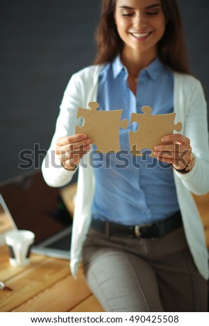 Business woman holding and pointing to a puzzle piece