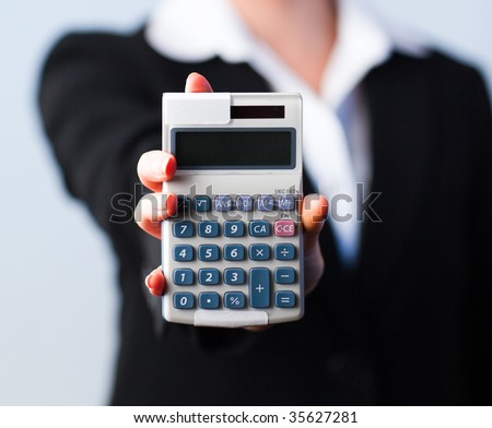 Business woman holding calculator out to the camera with focus on calculator - stock photo