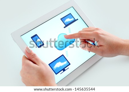 Business woman holding digital tablet computer with cloud computing theme on the screen and touching