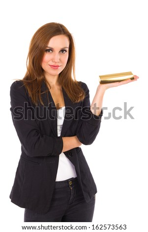 Business woman holding gold ingot and looking at camera. Three quarter length studio shot isolated on white.