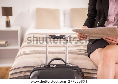 Business woman holding newspaper while sitting on bed near suitcase at the hotel room. Close-up. - stock photo