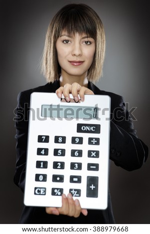 business woman holding out a large calculator - stock photo