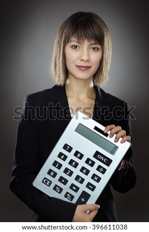 business woman holding out a large calculator