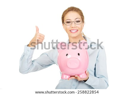 Business woman holding piggy bank with thumbs up. - stock photo
