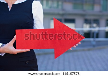 Business woman holding red arrow pointing to the right - stock photo