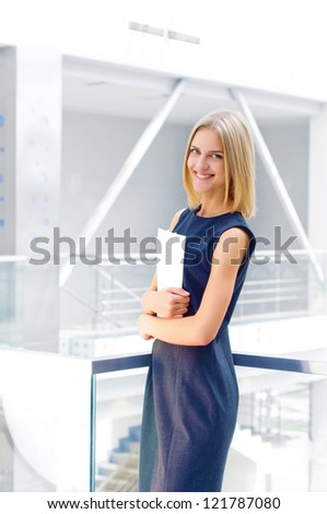 business woman holding reports and looking to the camera, copy space - stock photo