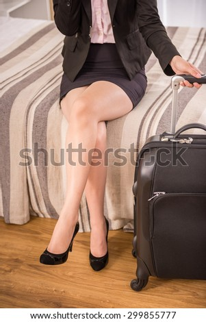 Business woman holding suitcase while sitting on bed at the hotel room. Close-up.