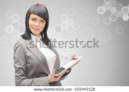 Business woman holding tablet computer on grey background. Working on touching screen.