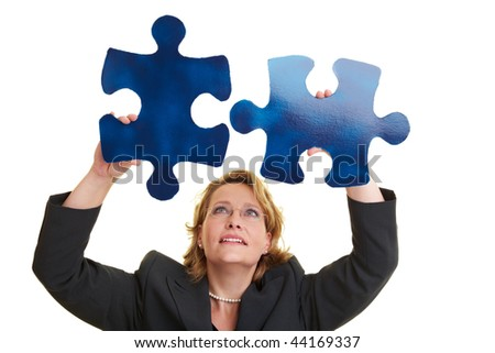 Business woman holding two blue jigsaw pieces