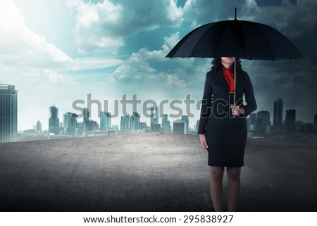 Business woman holding umbrella standing on the rooftop of the building