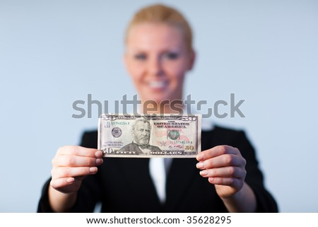Business woman holding up dollars with camera focus on the dollars - stock photo