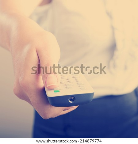 Business woman holds a remote control in her hands with her body out of focus with Instagram style filter