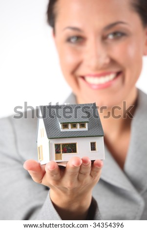 business woman holds model of house