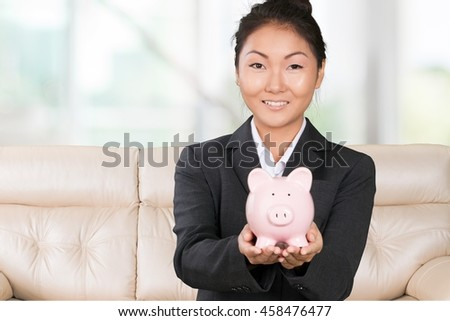 Business woman holds piggy bank.