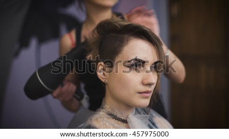 Business woman in a beauty salon, her makes hair styling. Professional master hairstyles working hairdryer and comb. - stock photo