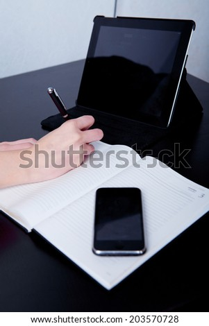 business woman in a cafe making notes in a diary, on the background of the phone and tablet