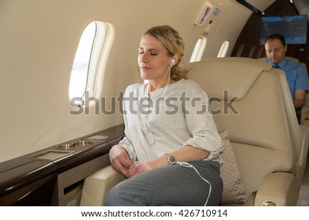 Business woman in a corporate jet relaxing and listening to music - stock photo