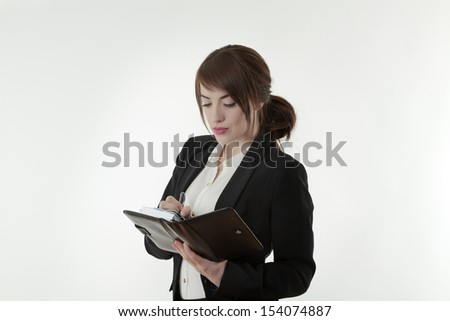 business woman in a sharp suit holding a note book working hard shot in the studio