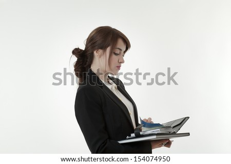 business woman in a sharp suit holding a note book working hard shot in the studio - stock photo