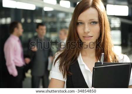 Business woman in an office with her colleagues on the background