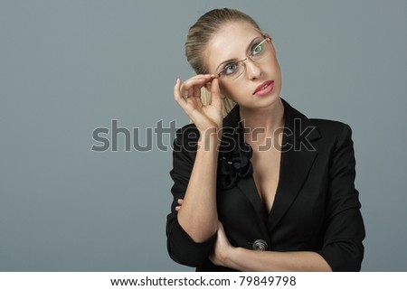 Business woman in black dress against grey background