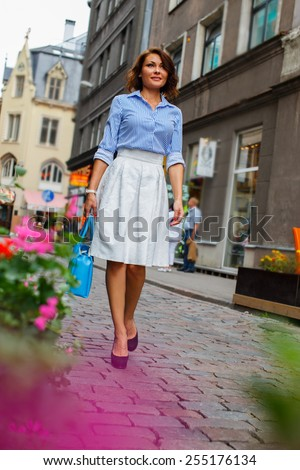 Business woman in blue blouse and white skirt wolking the city streets. - stock photo