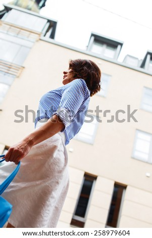 Business woman in blue blouse and white skirt wolking the city streets.