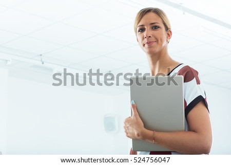 business woman in elegant dress holding a tablet in an office workplace