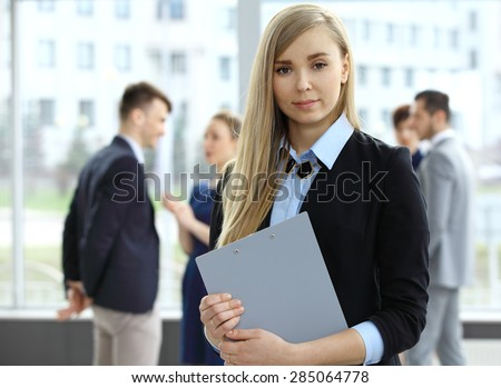 Business woman in foreground and her coworkers discussing business - stock photo