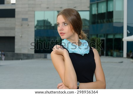 Business woman in formal attire is standing against a background of modern building facades