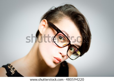 business woman in glasses looks attentively, portrait, isolated on gray background