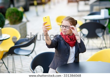 business woman in glasses sitting at a table in a cafe and makes Selfie. - stock photo