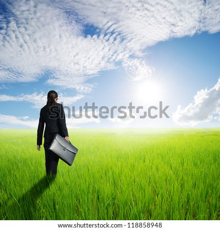 Business woman in green rice fields and Sun sky