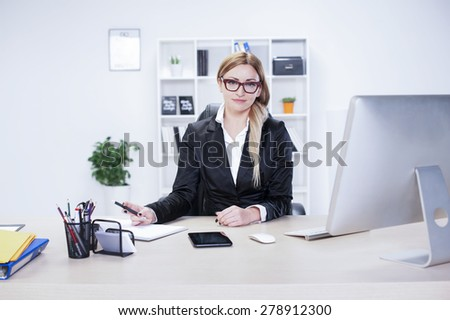 Business woman in her mid thirties sits at a desk in front of a computer screen - stock photo