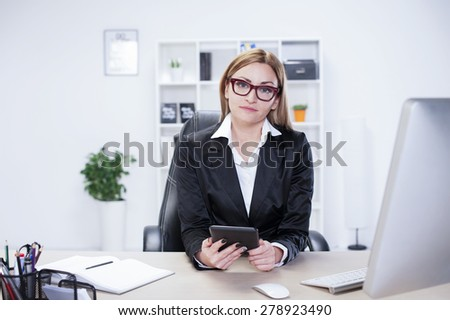 Business woman in her mid thirties sits at a desk in front of a computer screen holding tablet - stock photo